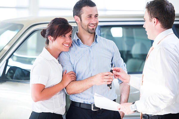 Smiling couple financing a new car from a dealership