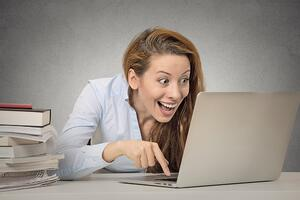 Very excited woman using electronic Bill Pay | First Alliance Credit Union