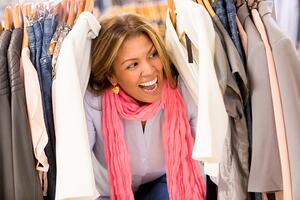 Excited woman shopping clothes on sale at retail store