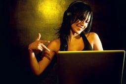Happy woman sitting behind laptop screen