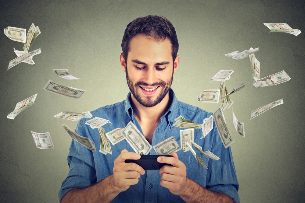 Man watching money fly from his phone