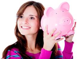 Smiling woman shaking a piggy bank
