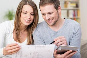 Young couple planning a new purchase together holding a calculator and the husbank pointing to a document held by the wife   First Alliance Credit Union