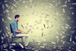 Young man with laptop and money in the air