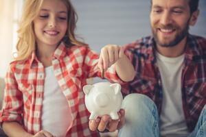 Smiling couple putting money in a piggy bank   First Alliance Credit Union