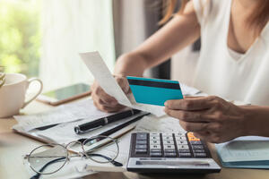Woman paying off debts and holding credit card