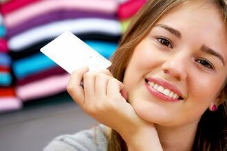 woman smiling and holding a credit card in a shop   First Alliance Credit Union