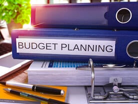 Blue ring binder with budget planning printed on it. | First Alliance Credit Union