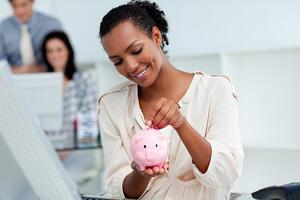 Joyful businesswoman saving money in a piggy-bank at her desk