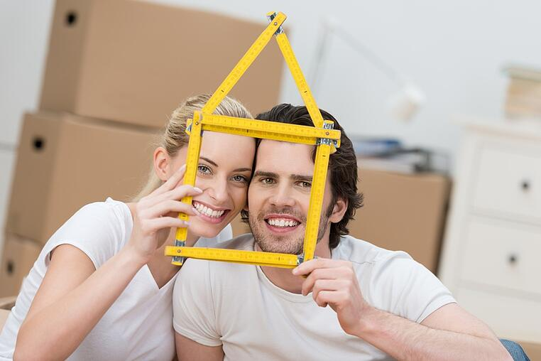 Young couple dreaming of their new home grinning as they hold up a builders ruler shaped as the frame of a house as they pose in front of stacked brown cartons in anticipation of a move.jpeg