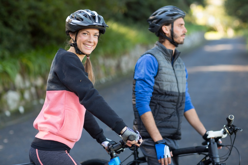 Biker couple with mountain bike on the countryside road