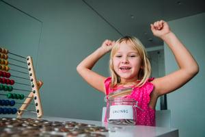 Girl saving money | First Alliance Credit Union