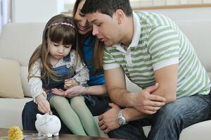 parents showing young child how to budget using a piggy bank | First Alliance Credit Union