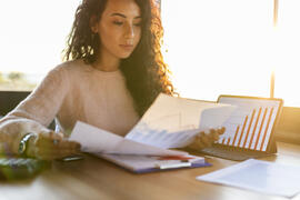 Woman studying investment information | First Alliance Credit Union