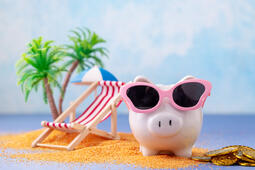 Piggy bank in sunglasses by the beach