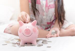 Girl and Piggy Bank | First Alliance Credit Union