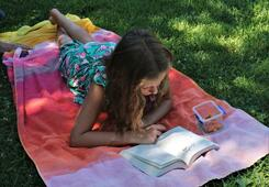 Girl on a blanket outdoors, reading a book